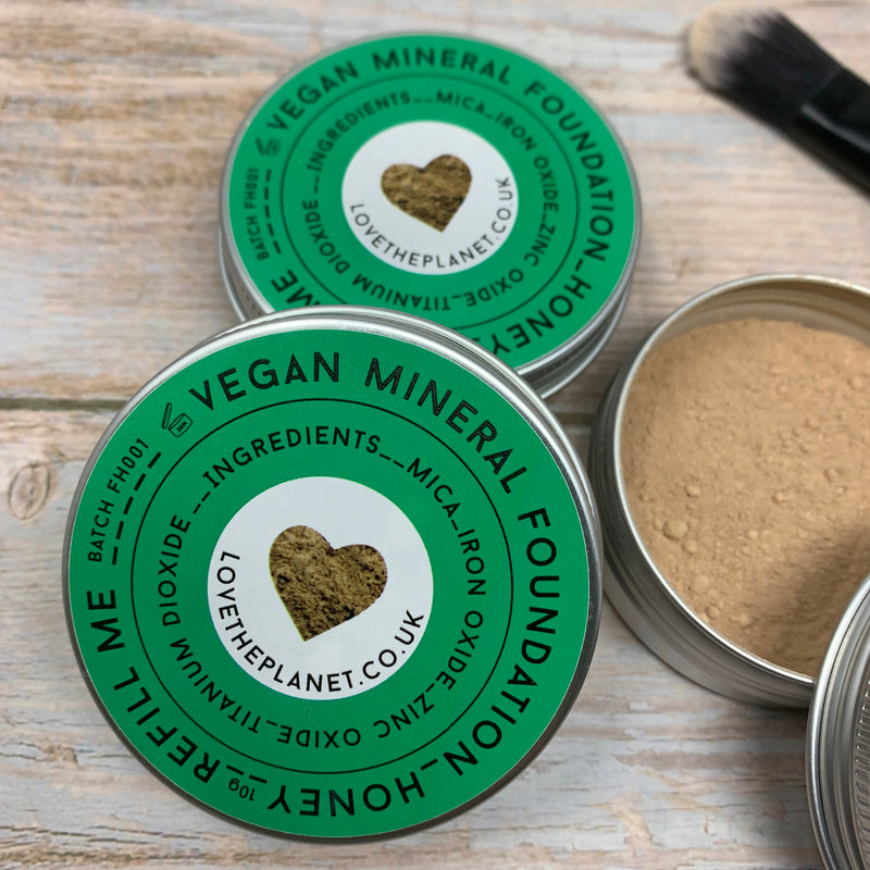 honey vegan foundation powder by love the planet, in reusable round metal tins with green coloured caps and a plastic-free foundation brush