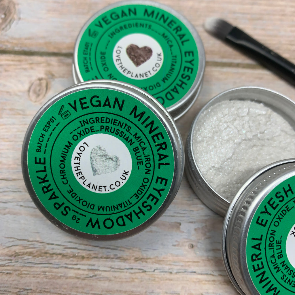 vegan mineral eyeshadow in metal tins and powder form, metal tins with green cap and make up brush