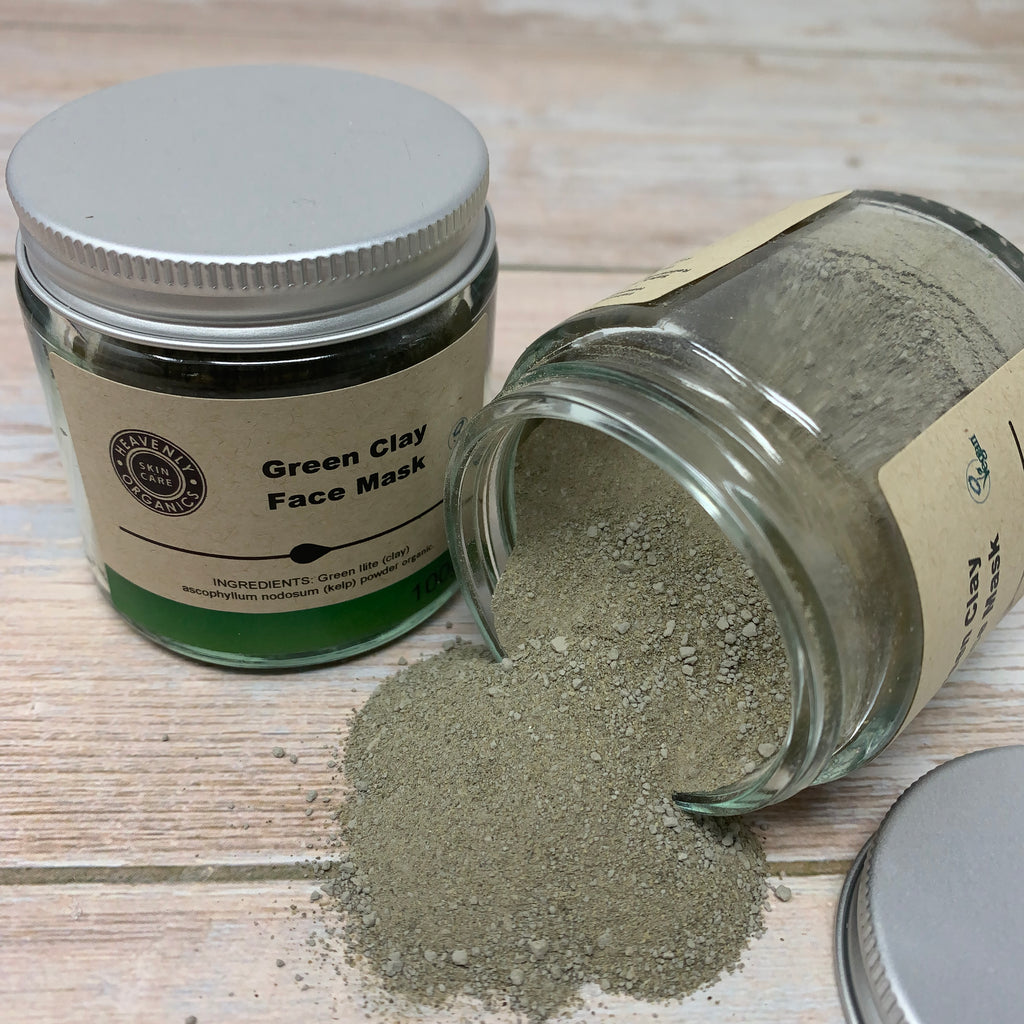 two jars of green clay face mask, one closed and one reclined with powdered green clay spilling on wooden table.