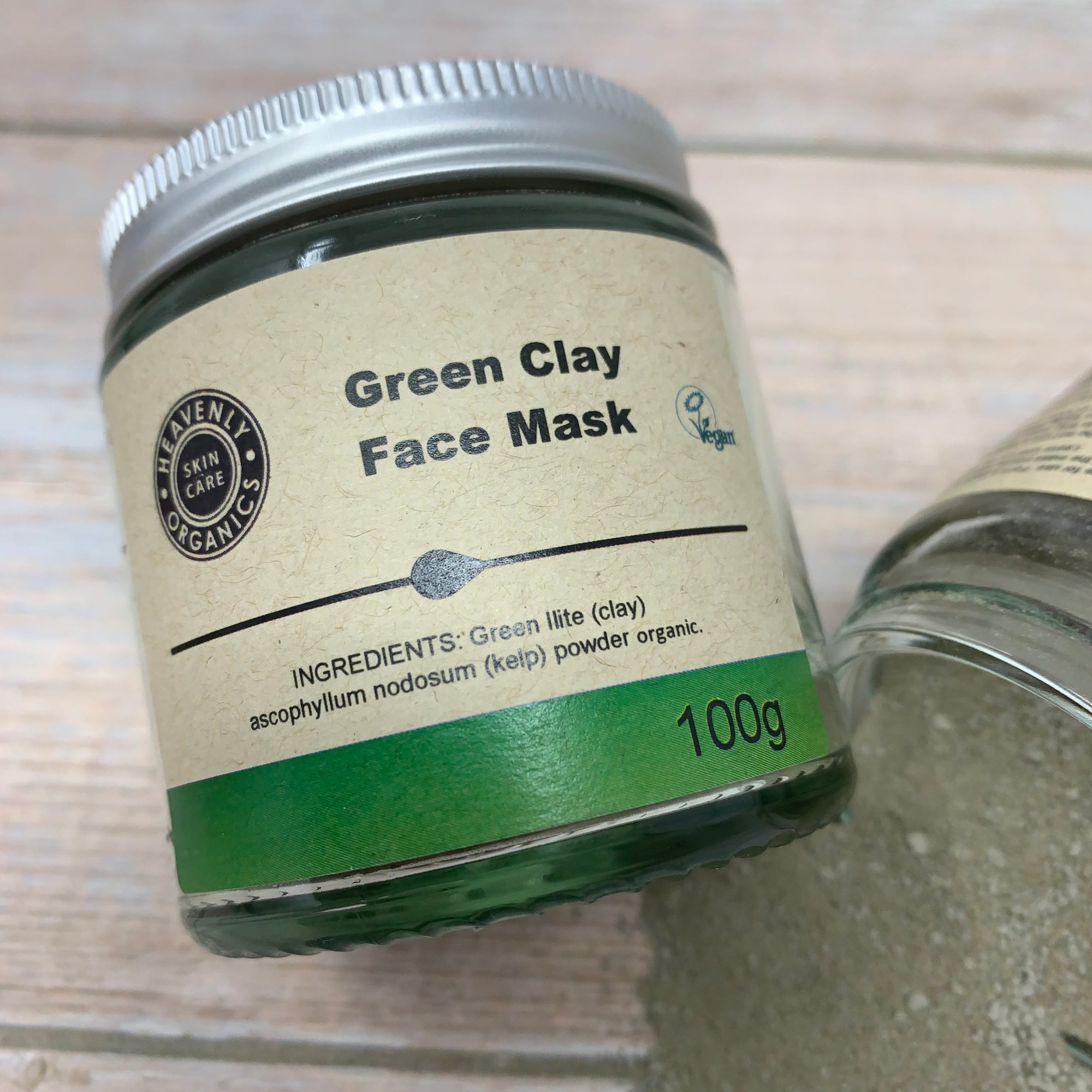green clay face mask in a glass jar and metal cap with green and cream coloured label by heavenly organics