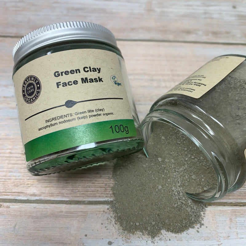 green clay face mask glass jars with mask powder poured on a wooden surface table