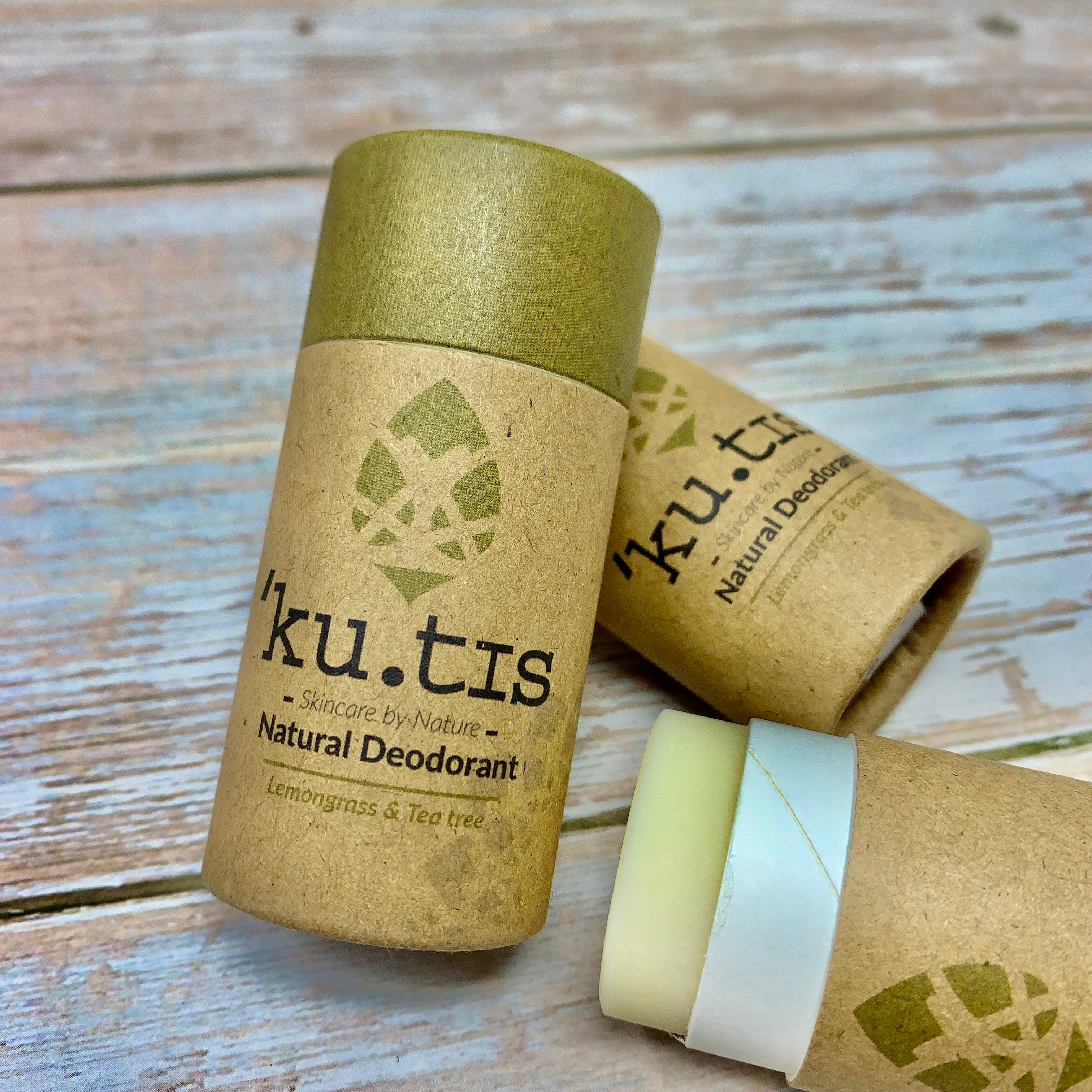 natural deodorant in cardboard tube by kutis, green and brown container and open deodorant with lemongrass and tea tree formula