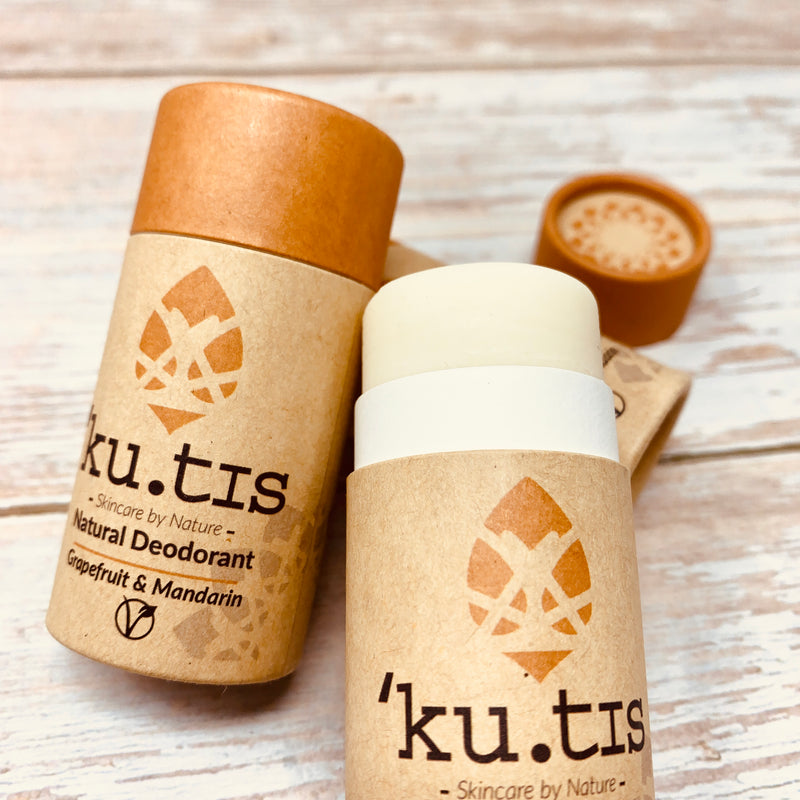 kutis vegan deodorant in a cardboard tube with orange cap, one deodorant is open to show the inside white stick