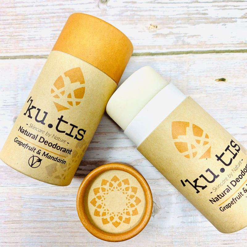two ecofriendly grapefruit and mandarin deodorant sticks by kutis on wooden table