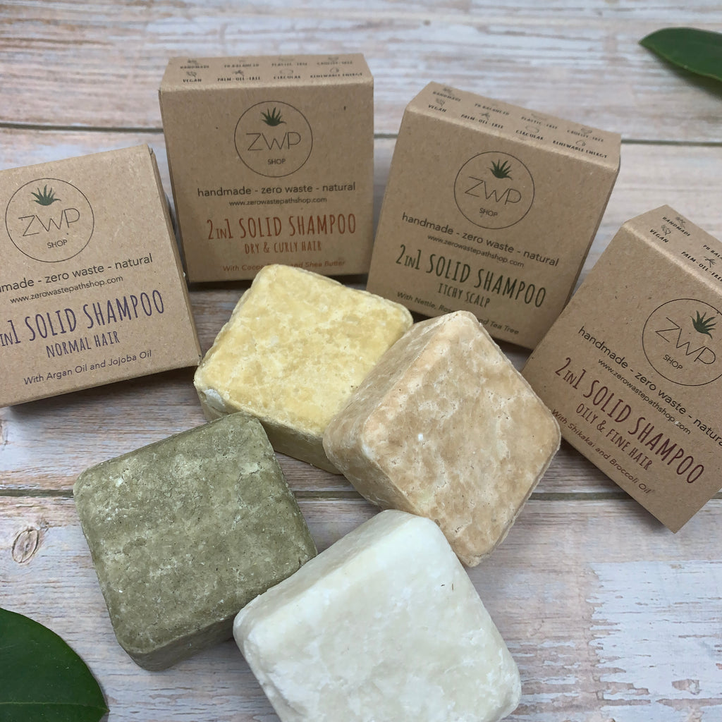 four 2-in-1 natural shampoo and conditioner bars with recycled brown boxes