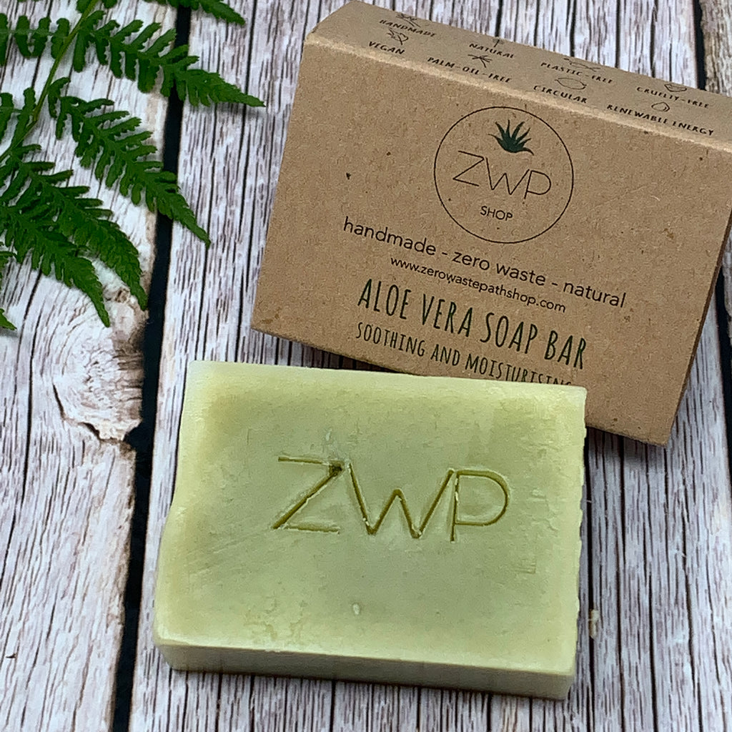 "green aloe vera soap bar by zero waste path with logo on surface and plastic free brown box with words ""aloe vera soap bar - soothing and moisturising"" on the front"