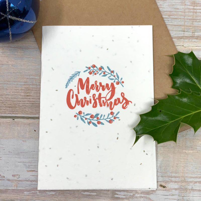 merry christmas card made with recycled paper and seeded cardboard to grow flowers