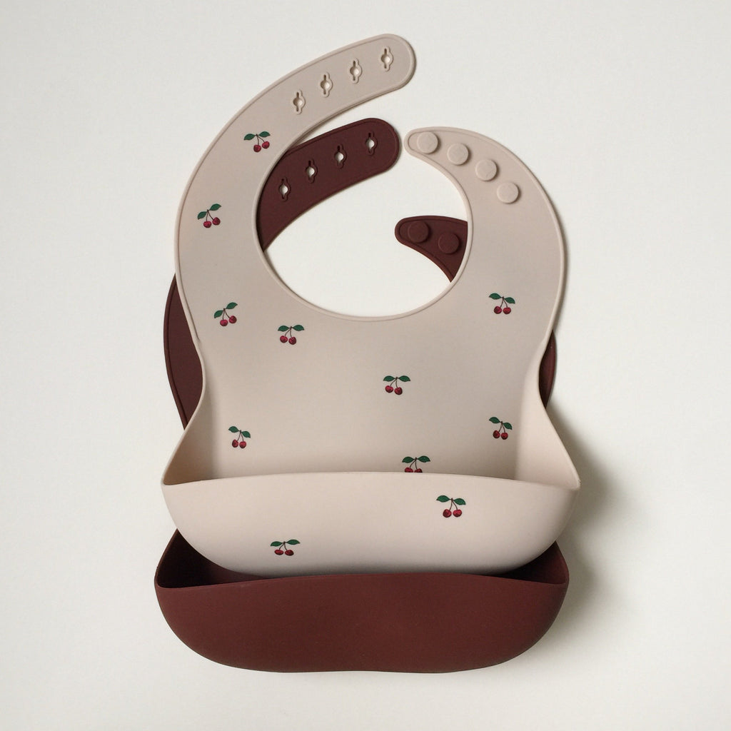 2 pack of Silicone feeding bibs from Danish design house Konges Slojd- one with cherry print and one plain mocca.
