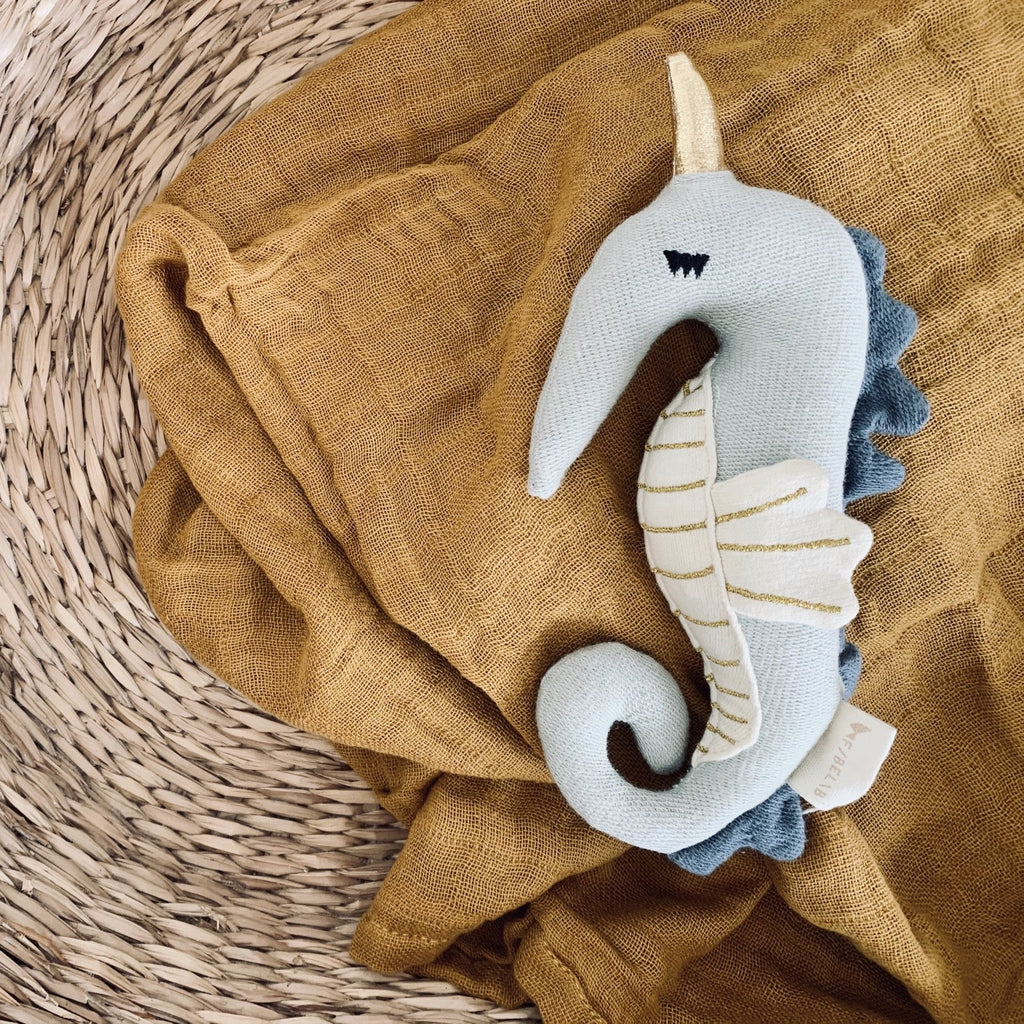 seahorse rattle from Danish brand Fabelab. a beautful soft and gender neutral rattle in blues with gold detailing. made from organic cotton and super soft on a little ones's delivare skin