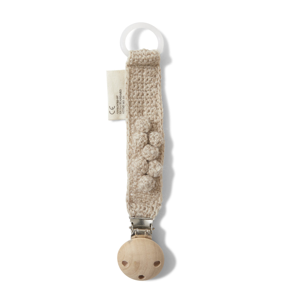 Knitted Dummy clip from Konges slojd - This organic soft wool pacifier strap is a practical chain to keep your little ones dummy safe and falling on teh floor when you're out and about. Available in creamy white, cacao brown, rose blush and almond.