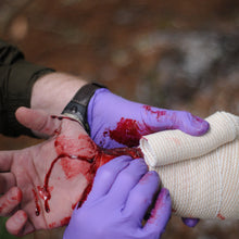 Load image into Gallery viewer, A Wilderness First Responder Recertification (WFC) student practicing bleeding control and wound management.