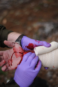 A Wilderness First Responder Recertification (WFC) student practicing bleeding control and wound management.