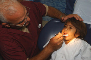 Remote EMT assessing a child's dental needs