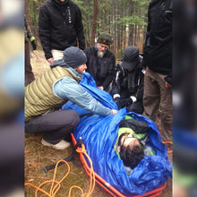 "Load image into Gallery viewer, Wilderness First Aid (WFA) students learn how to create a ""hypo-wrap"" to protect patients from the environment in Remote Medical Training courses."