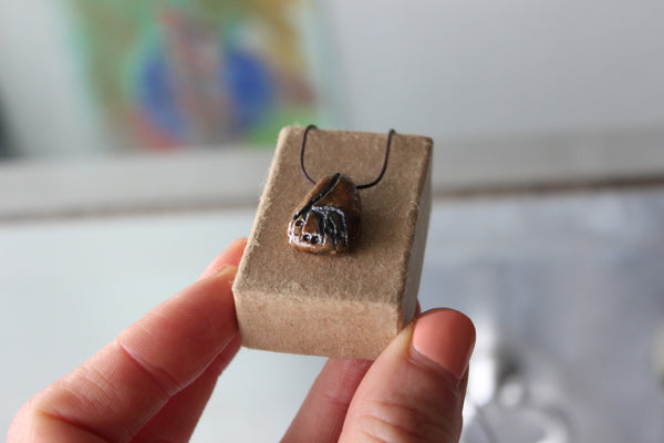small ceramic pendant with a plant