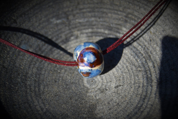 Ceramic pendant necklace with a single bead