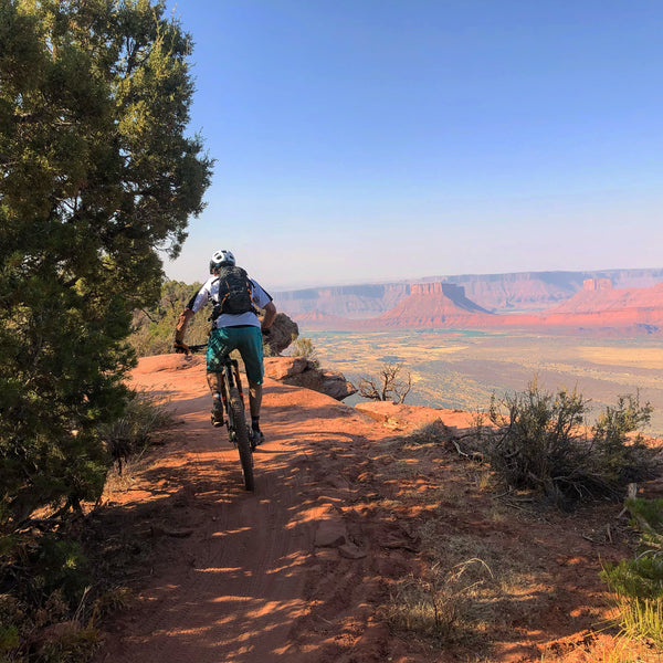 Mountain biker rides along rim of the canyon in Moab Utah. The Whole Enchilada Trail.
