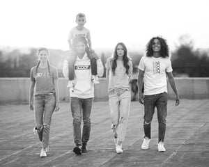 A group of friends walk together wearing original branded t-shirts.