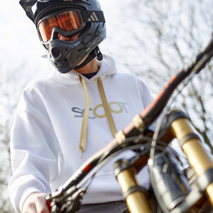 A downhill mountain biker poses on his bike while wearing a hoody and a full face helmet with goggles.