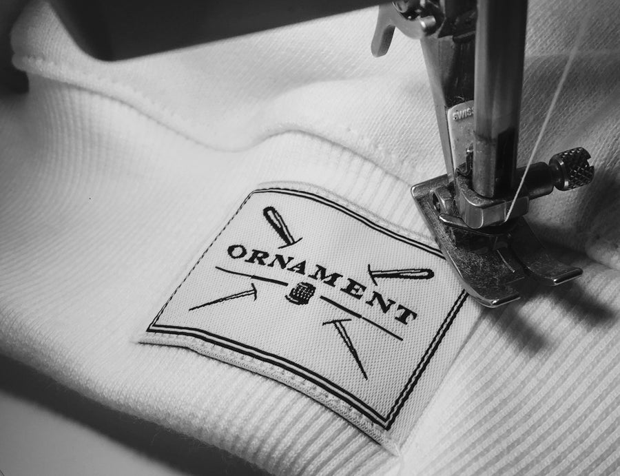 Ornament philosophy black and white logo label on fabric with sewing machine