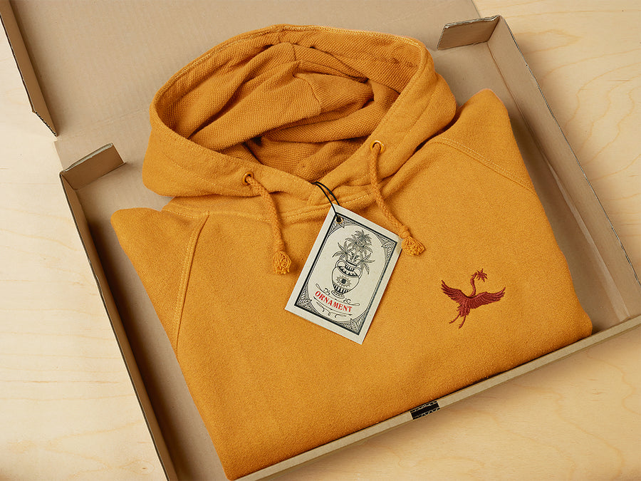 Sustainable hemp and bamboo hoodie in yellow with crane embroidery on chest in recycled box