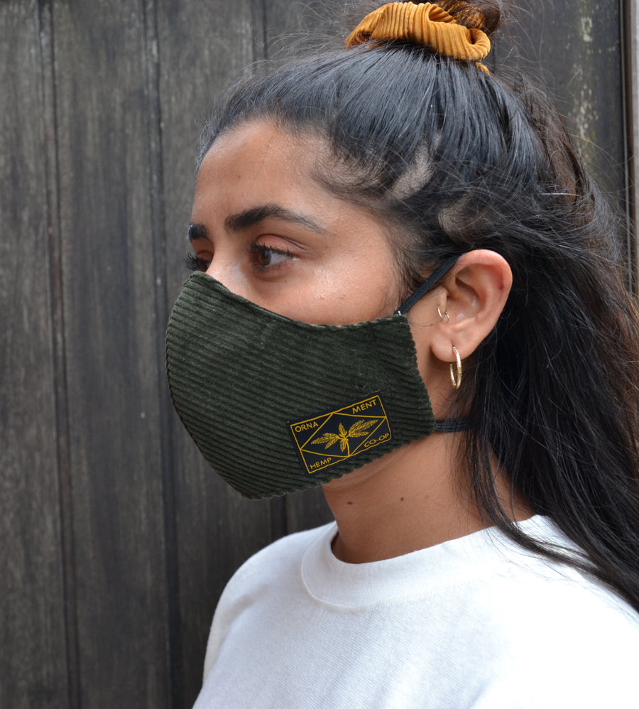 Sustainable Hemp face mask in velvet green corduroy fabric with yellow hemp label on female