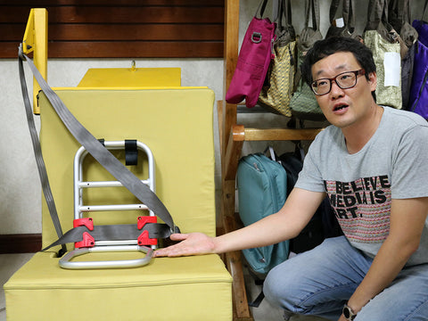 Engineer I.S. Choi reviews the original Pico travel car seat frame and safety belt position
