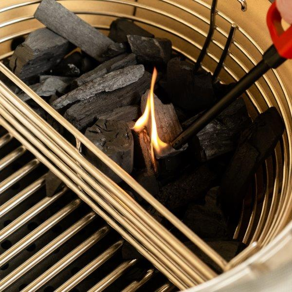 Lighting charcoal in one side of the divided basket