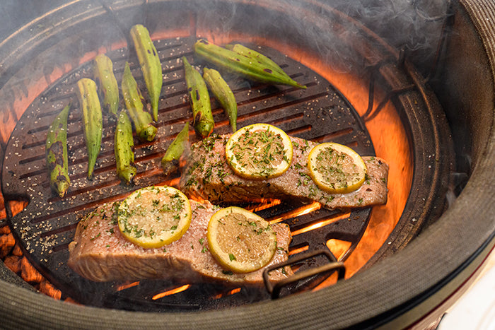 Salmon and okra being cooked to perfection on the Kamado Joe® Sear Plate