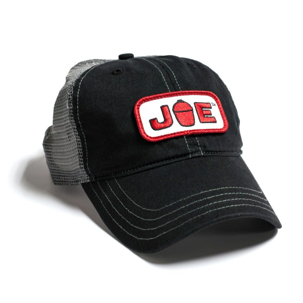 "Bill cap with black fabric front and charcoal mesh back. Front features a white and red patch with the Kamado Joe ""JOE"" logo."