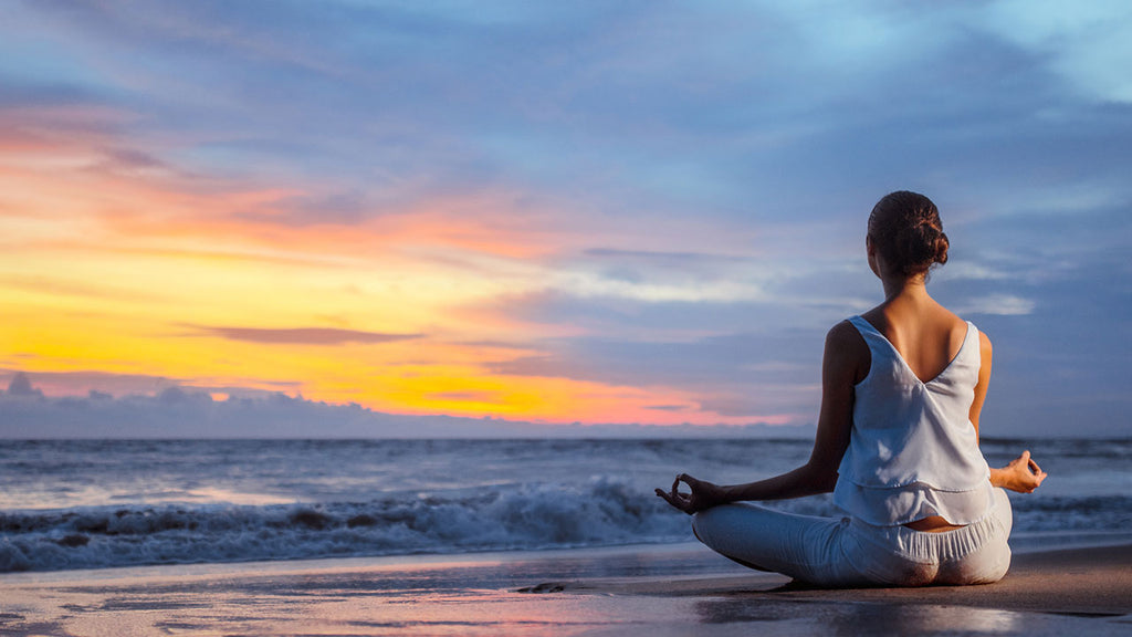 Woman sitting on the beach meditating at sunset