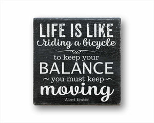 life is like riding a bicycle to keep your balance you must keep moving box sign