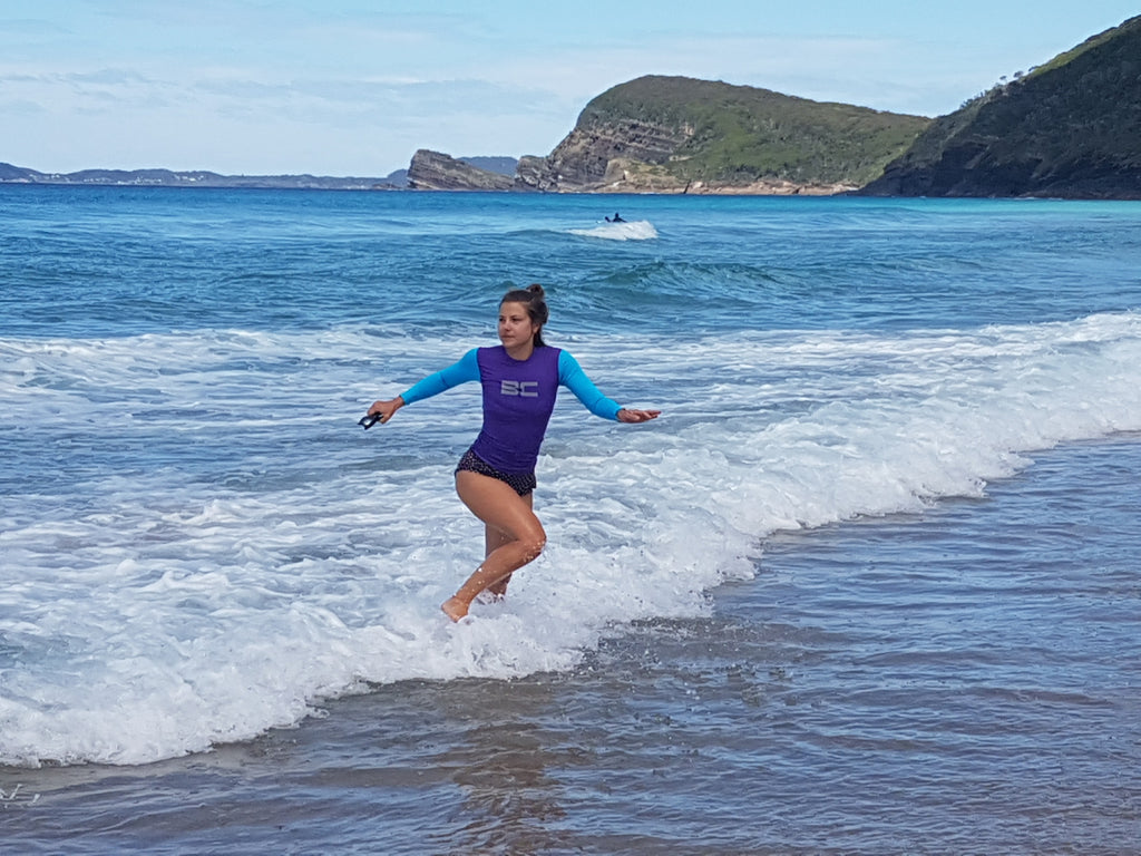 girl running out of the sea in BC rash vest