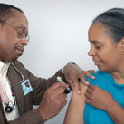 A picture of a doctor injecting the flu jab into the arm of a woman