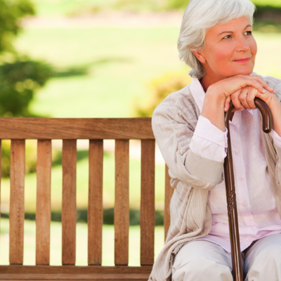 Woman sat on bench with with walking stick