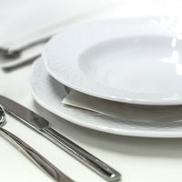 Dining set of white plates with cutlery and glass