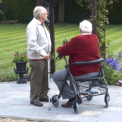 Two gentlemen, one with walking stick and one with bariatric rollator chat in a garden