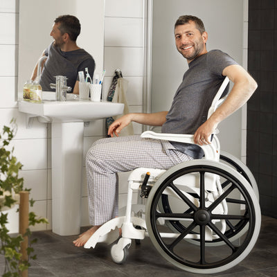Man in self propelled shower commode chair