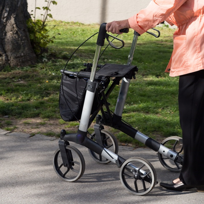 Lady strolls through the park with a four wheel rollator