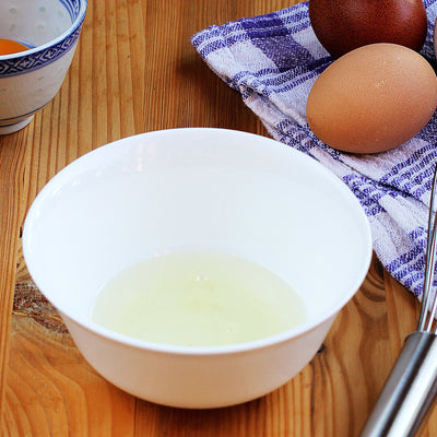 Cracked egg in bowl next to whisk and tea towel with more eggs