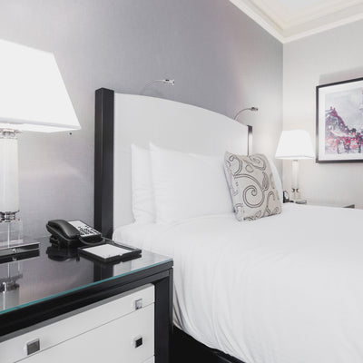 White profiling bed next to bedside cabinet with lamp