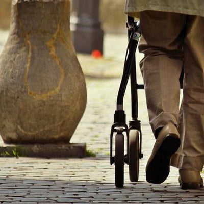Man using wheeled rollator walking aid in cobbled street