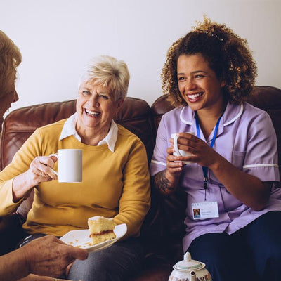 Female carer and two senior ladies laugh while having tea and cake