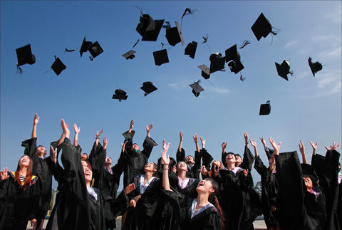 the image shows A collection of students, all dressed in gowns, throwing their graduation hats into the air