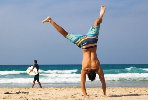 the image shows a man doing a cartwheel on a beach
