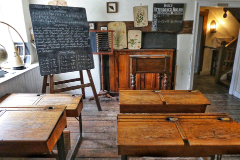 the image shows An old fashioned school room with some wooden desks and a blackboard that has some scribbles all over it