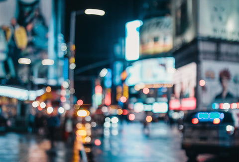 the image shows a blurred vision view of a busy city at night