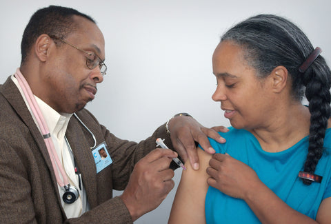 the image shows a doctor giving someone the flu jab