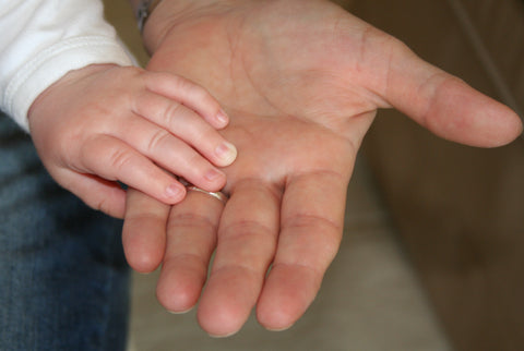 the image shows a child holding hands with an adult