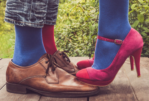 Some brown men's shoes with a men wearing some blue and pink socks and some pink, women's stilettos with the woman wearing blue socks